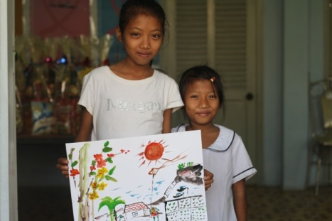 Thuy and Nhu with picture of their dream house.